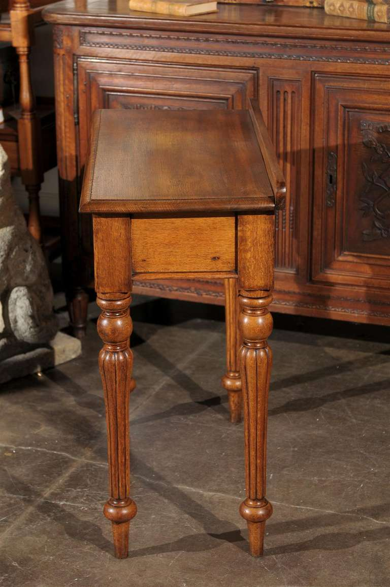 English 1880s Oak Console Table with Single Drawer, Shield Motif and Reeded Legs For Sale 4