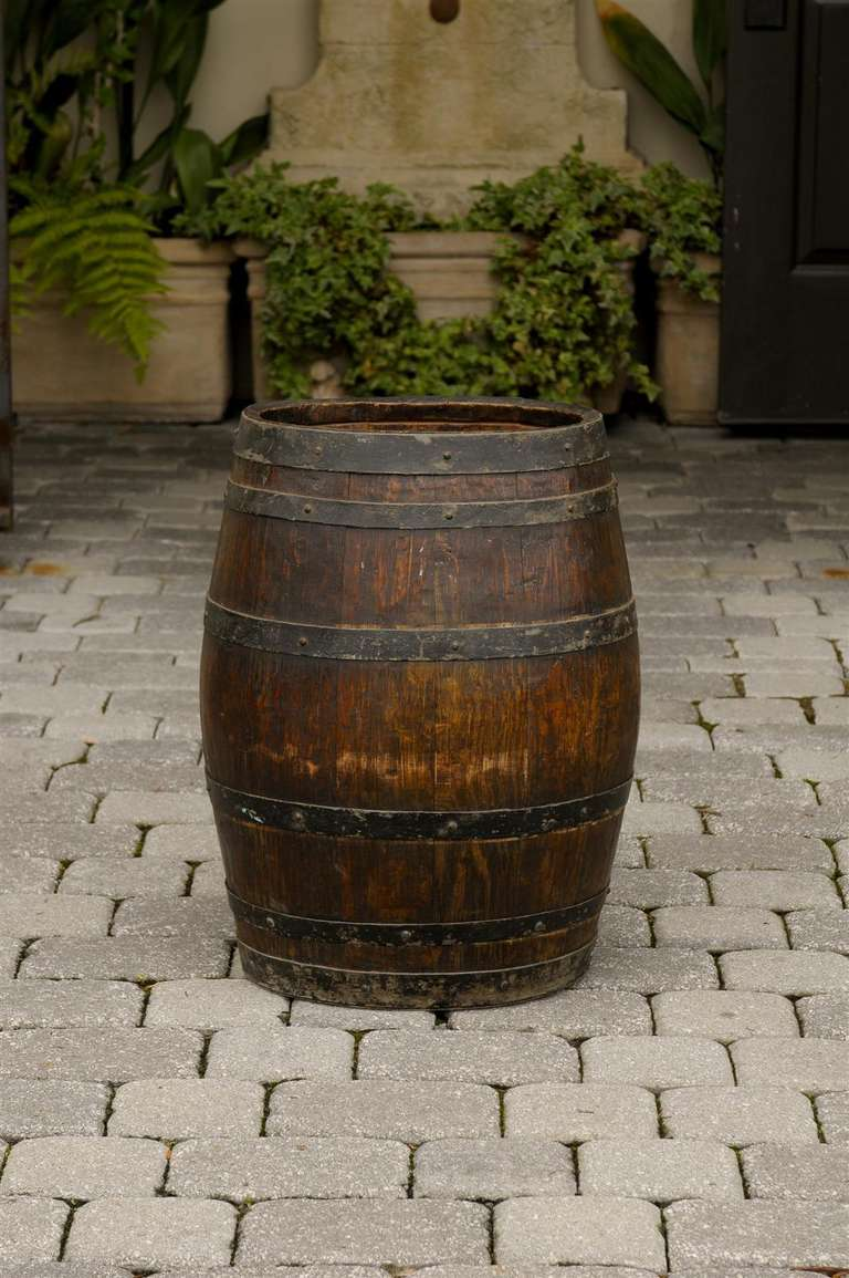 An English wooden rustic barrel with metal straps. This late 19th century barrel is made of vertical wooden slats - possibly oak - secured by six horizontal iron bands.  Given the strength of its construction this barrel may have been used to