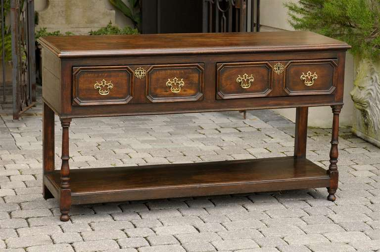 This English oak sideboard from the mid-19th century features a rectangular top over two drawers, decorated with brass Chippendale style hardware. Each drawer is adorned with a raised geometrical molding, creating perfect symmetry and balance and