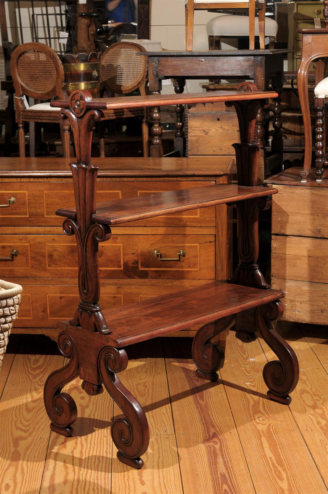 This mahogany tiered shelf from the late 19th century features three shelves over exquisite S-scroll legs. While the wooden rectangular shelves are simple in shape, the eye is immediately drawn to the lateral supports. It all starts with the volutes