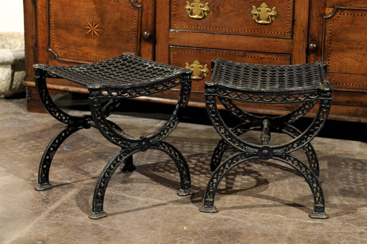 A pair of iron Belle Epoque style garden stools from France, 20th century. These curved cross framed stools, with their industrial style and filigreed legs can't help but bring to mind the France of the late 19th century, as embodied by Gustave