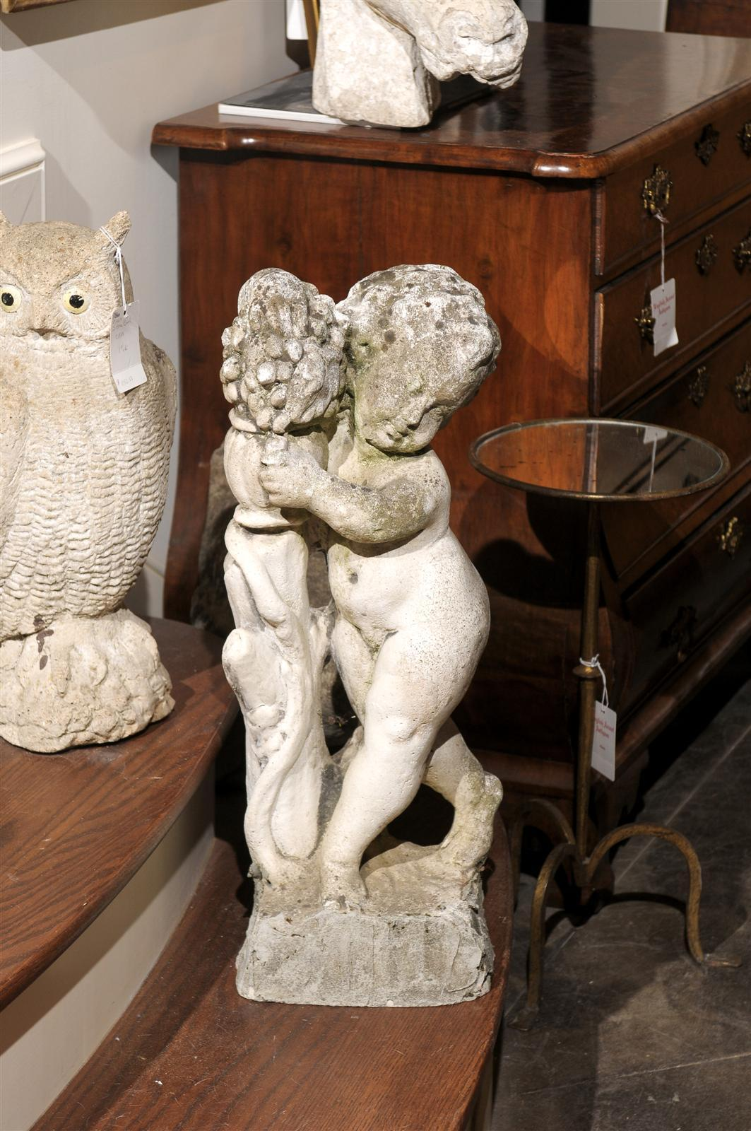 This delightful French stone statue from the mid 20th century, features a small putto figure leaning against a trunk holding a vase and grapes. Perhaps one of the followers of the god Bacchus from the Greco-Roman mythology, this cheeky cherub seems