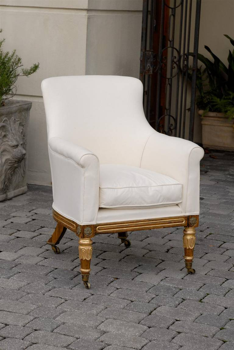 This English early 19th century period Regency armchair features a new muslin upholstered curved back, seat with cushion and arms over four exquisite short painted legs with gilded accents. The front two legs are tapered and decorated with gilded