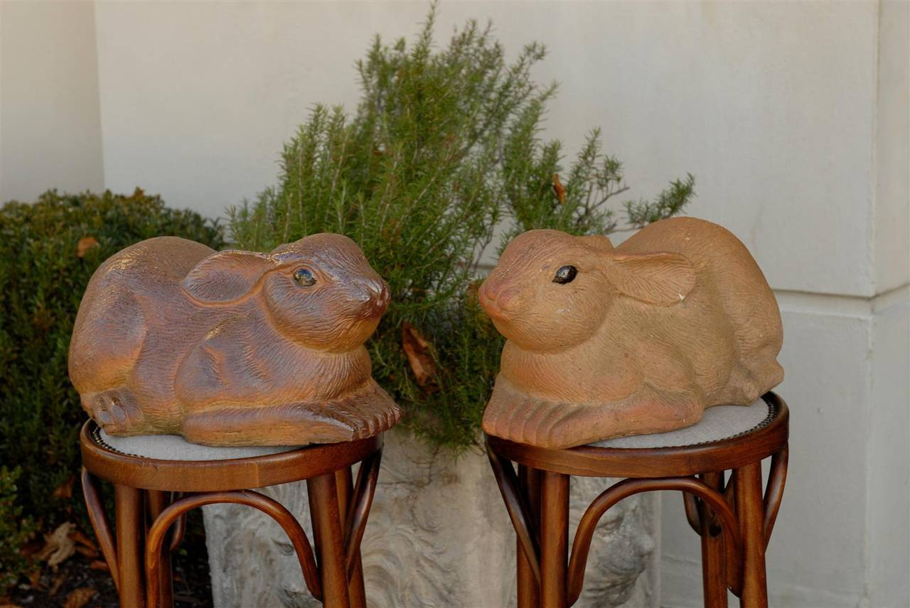 A pair of vintage painted terracotta rabbit sculptures from midcentury, England. Each rabbit displays an enjoyable lively posture, resting on their front feet with their ears laying back. The hairs are carved with a great attention to details, while