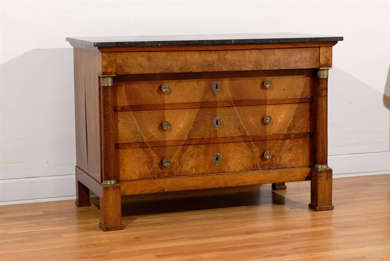 This exquisite French commode from the early 19th century features a dark grey marble top over four drawers. The lower three drawers are recessed and flanked by elegant columns with bronze Doric capitals and bases, typical of the classical taste of