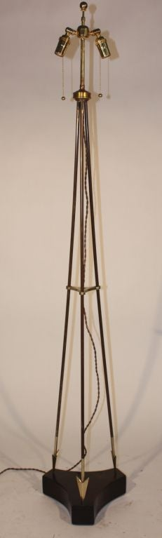 A rare tripod floor lamp attributed to Jacques Adnet comprised of three brass and patinated bronze arrows on an ebonized wooden base.