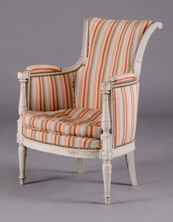 A nice French Directoire Period painted bergere chair, circa 1800, the outscrolled top rail above padded armrests and upholstered sides, with baluster-shaped supports, raised on baluster-shaped legs, in old grey painted finish.