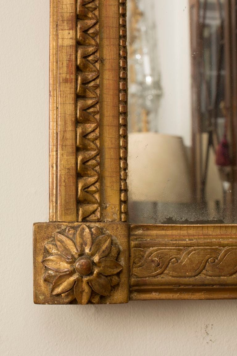 The rectangular mirror plate within a bead and reel border surmounted by musical instruments and foliage.