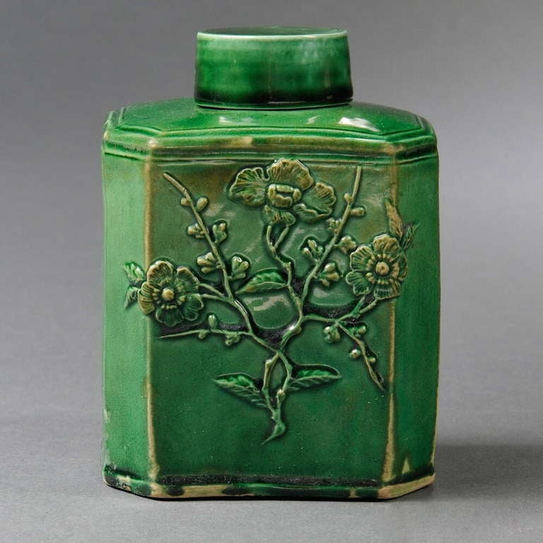 An 18th century English Staffordshire green glazed ceramic tea canister, circa 1765, inspired by Chinese metal and ceramic forms, of rectangular form with canted corners, with applied press-molded prunus blossom decoration to both sides, with cover.