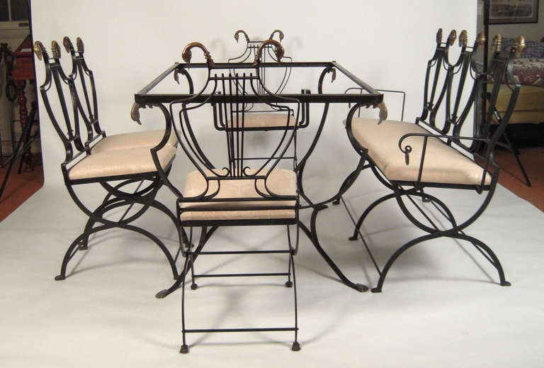 A neoclassical style/Hollywood Regency dining table and chairs (3 side chairs, 1 arm chair)  and settee for 6, the black painted wrought iron  iron lyre-back folding chairs with bronze swan's head decorations, over upholstered seats, raised on