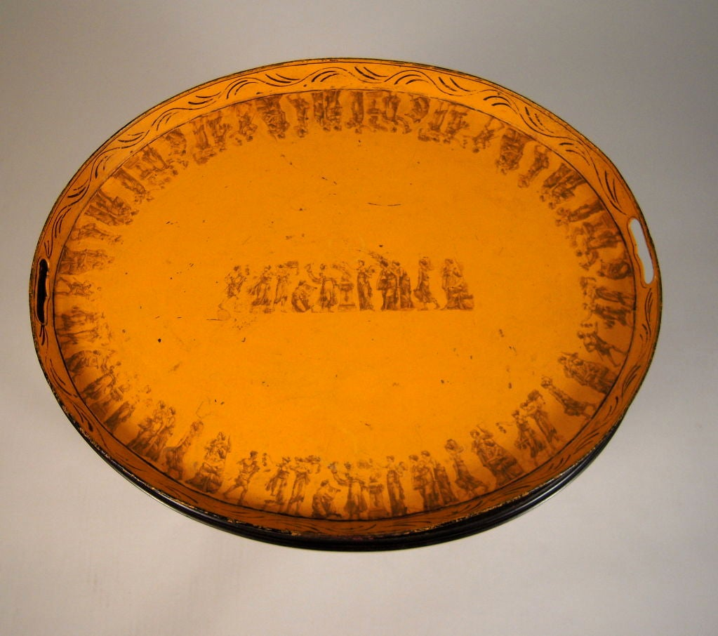 An early 19th century French yellow oval tole tea tray decorated with hand painted and transfer printed neoclassical ornament, on a later ebonized stand with turned faux bamboo legs joined by an X-shaped stretcher.