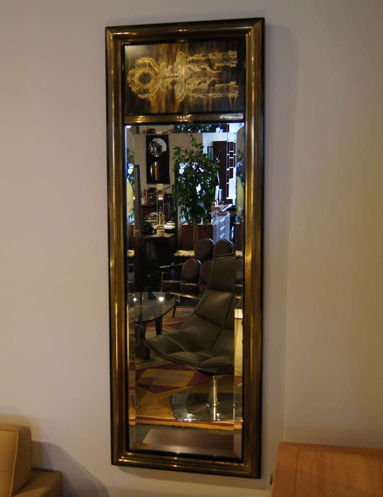 This beautiful mirror was designed by Bernhard Rohne for Mastercraft. The frame is composed of black lacquered wood with applied brass. It features Rohne's signature acid-etched brass designs above the long beveled mirror.