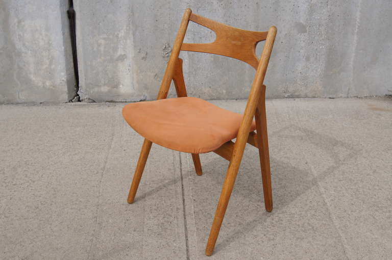 Hans Wegner's CH-29 uses a minimum of parts to create a sturdy but visually light chair. The unusual construction allows for a wider seat in the front; along with the curved backrest, this makes the chair extremely comfortable for long hours around