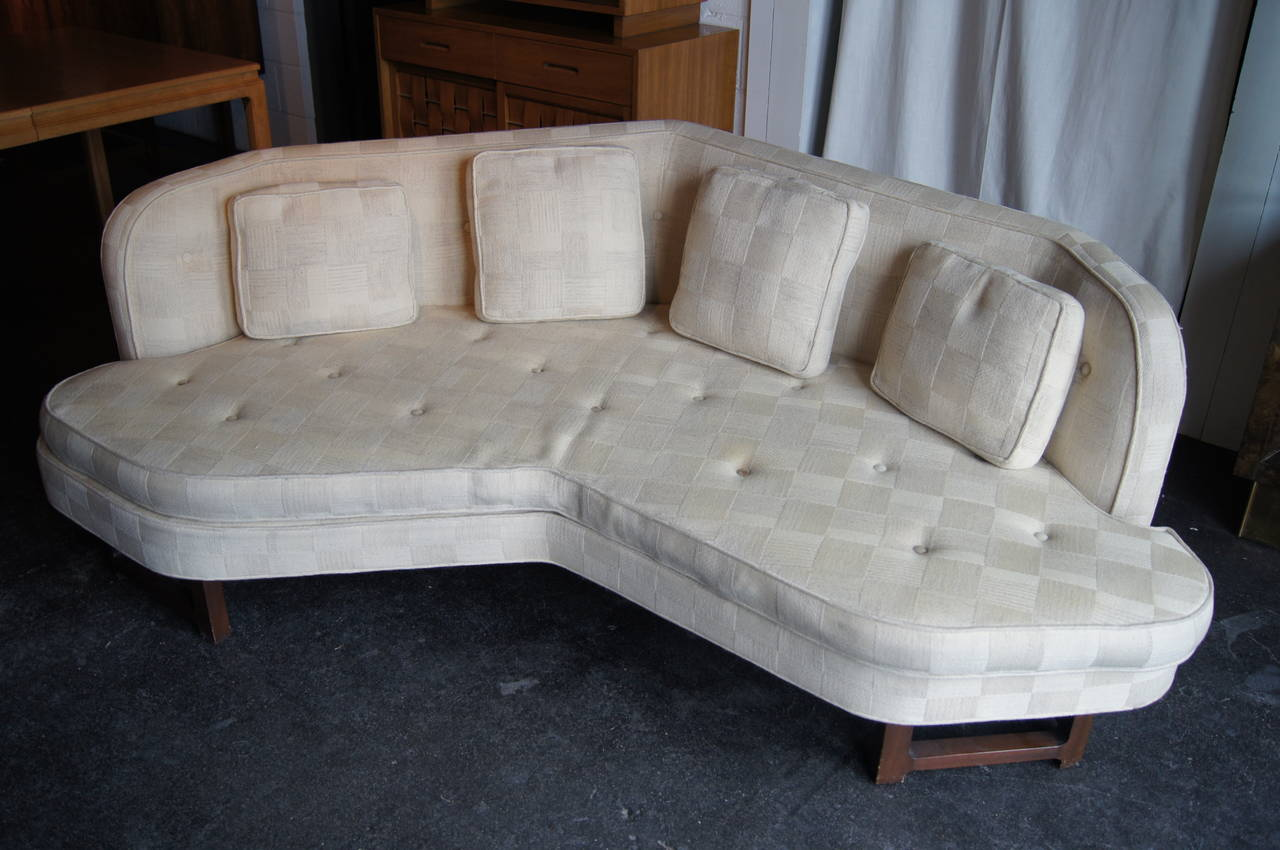 Edward Wormley designed this sofa, model 6329, as part of his famous Janus collection for Dunbar. Set on a sturdy mahogany base, the sofa's deep angularity gives it an arresting look and makes it a comfortable piece for both lounging and