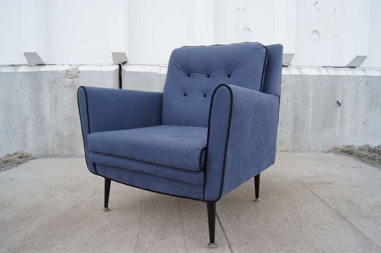 These handsome lounge chairs feature a distinctly 1950s silhouette with tapered black metal legs. They have been reupholstered in a soft blue microfiber with contrasting black piping.