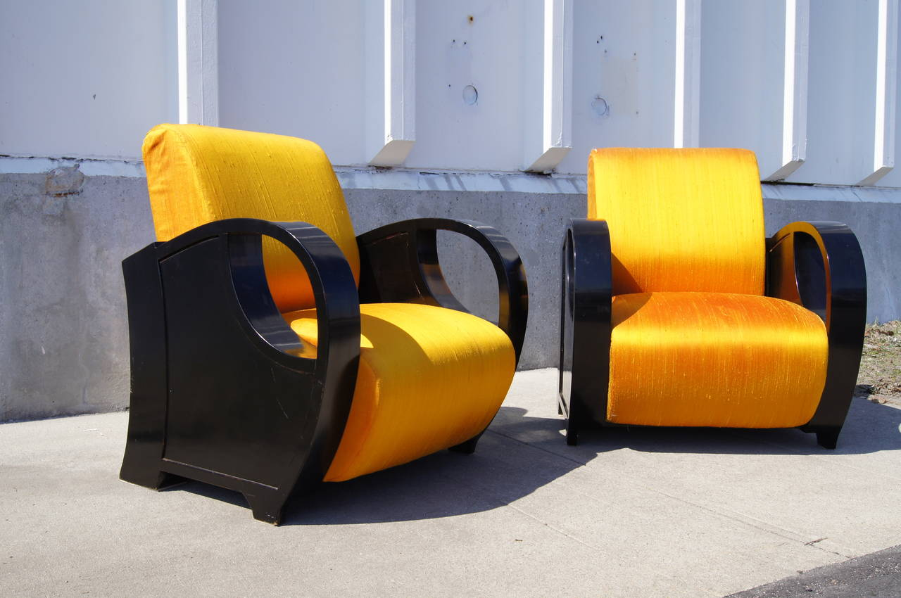 This pair of European club chairs are strong examples of Art Deco moderne. Their large curvaceous sides in ebonized wood frame generous, comfortable seats.   They are very solid and in excellent structural condition. They will need to be