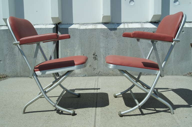 These folding chairs were designed by Warren McArthur and manufactured by Mayfair Industries. They are constructed of tubular aluminum and feature mauve leather upholstery.