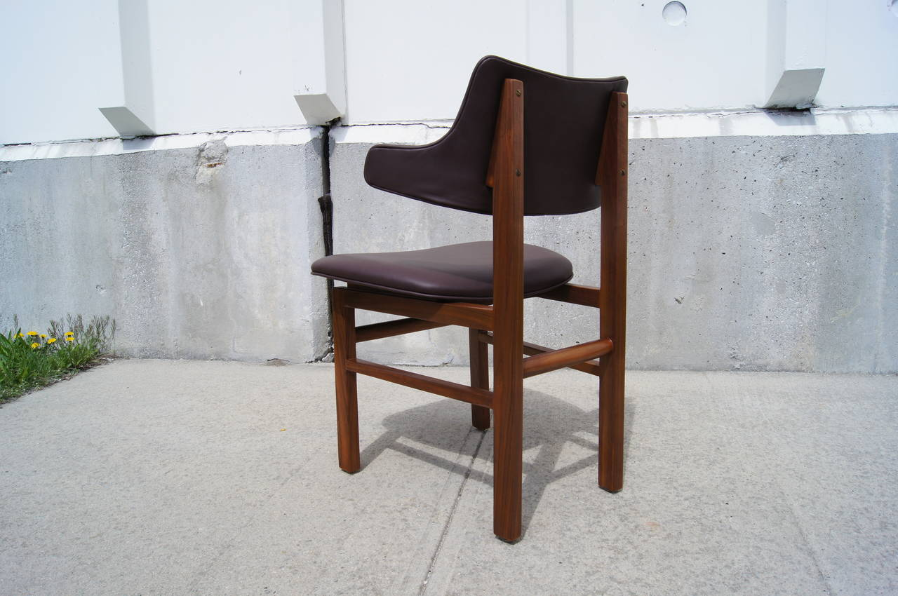 Edward Wormley designed these handsome leather and walnut dining chairs (model #675) for Dunbar with upholstered curved backs that are attractive from every view.  Their frames have expertly refinished to bring out the beauty of the walnut grain