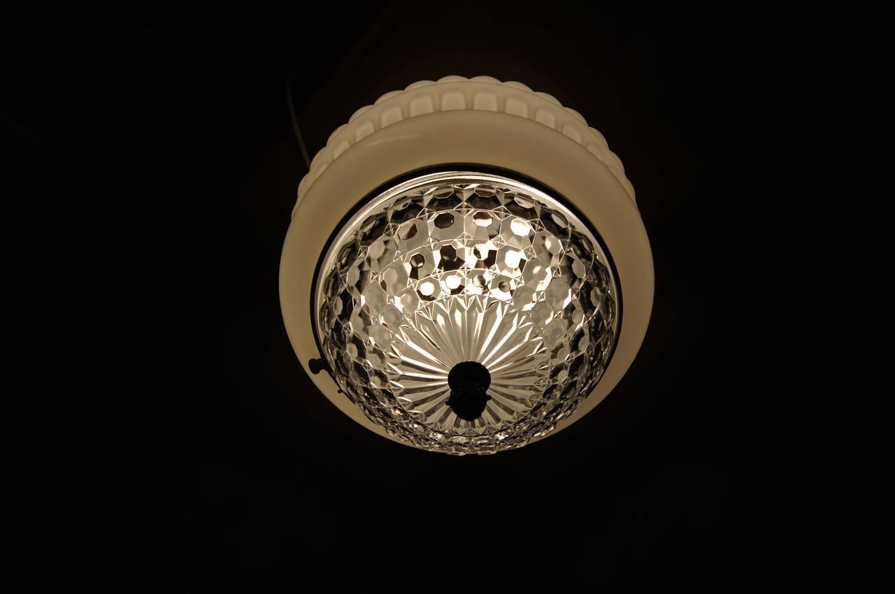 Made in Italy in the 1920s, this art deco ceiling lamp plays a black base and metal finial against a thick band of white opaque molded glass and a crystalline pressed glass center.