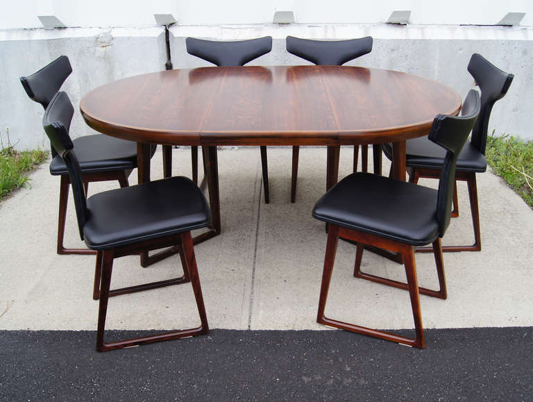 This dining set by Arne Vodder comprises a beautiful rosewood table and six sculptural T-back chairs. The table has a unique angled base and comes with a 19.5 in. leaf that expands the round top into an oval.   The chairs have been reupholstered