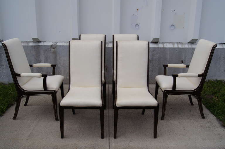 Designed by William Doezema, a cofounder of Mastercraft, this striking set includes two armchairs and four armless dining chairs. The chairs are constructed of beautiful dark amboyna burl wood with subtle brass inlay and are upholstered in an