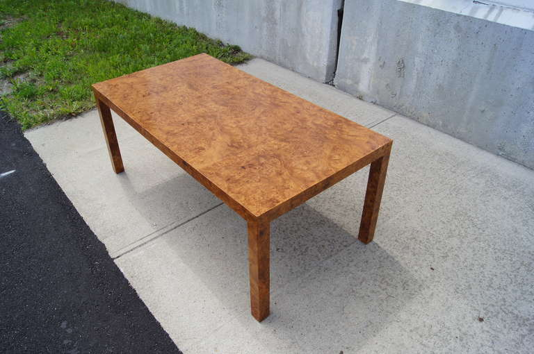 This Parsons-style coffee table was made in the 1970s by a Boston, Massachusetts, custom furniture company. The beautiful walnut burl wood enhances its clean lines.  Metal label underneath table.