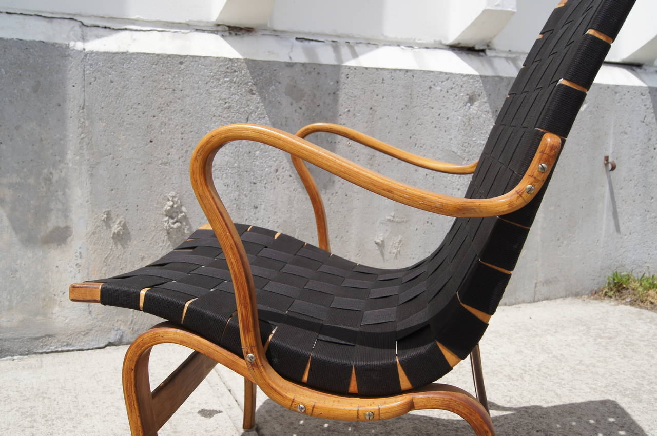 The Eva Chair, designed by Bruno Mathsson in 1934, comprises a cotton webbing seat on a serpentine birch frame. This example was restrapped with vintage cotton webbing and also also features a custom leather cover.
