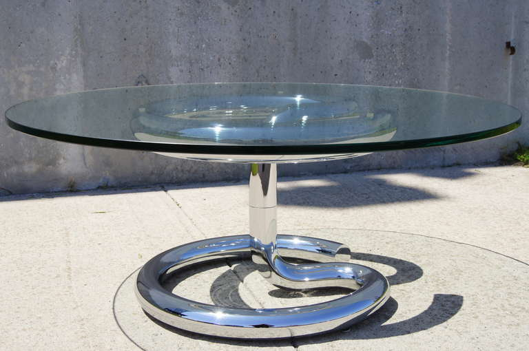 Designed by Paul Tuttle for Strässle International in the 1970s, the aptly named Anaconda Table features a muscular serpentine chromed steel base and a round glass top.   The diameter of the base is 22 inches, while the glass top is 40 inches.