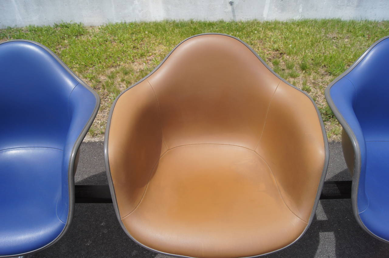 Charles and Ray Eames developed this tandem shell seating for Herman Miller in 1963 as a comfortable solution for heavily trafficked spaces. A row of three vinyl-upholstered fiberglass-reinforced armchairs, two in ultramarine and one in raw umber,