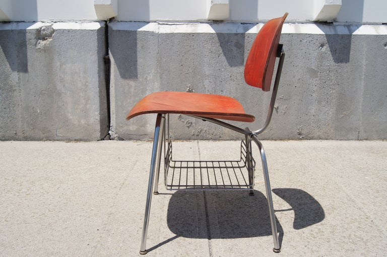 This rare iteration of the Eames's DCM side chair, produced by Herman Miller between 1950 and 1954, features a chrome wire magazine rack below the seat. The bent plywood is finished in aniline red. 