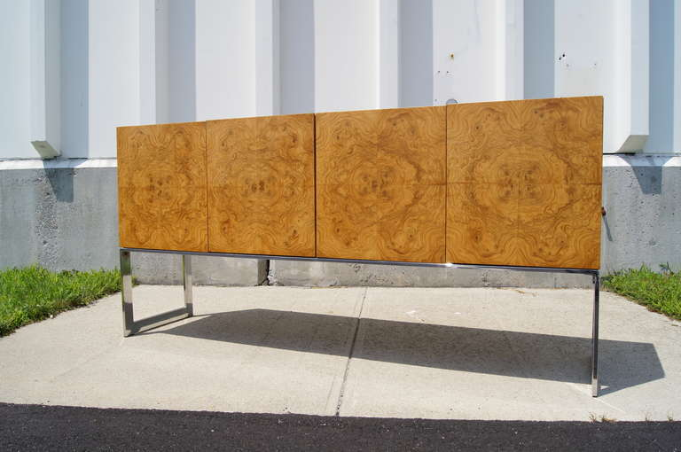 This sideboard by Milo Baughman is composed of a stunning burl wood cabinet that is set on a light chrome frame. One half of the sideboard features adjustable shelving, while the other half features two cutlery drawers and vertical storage.