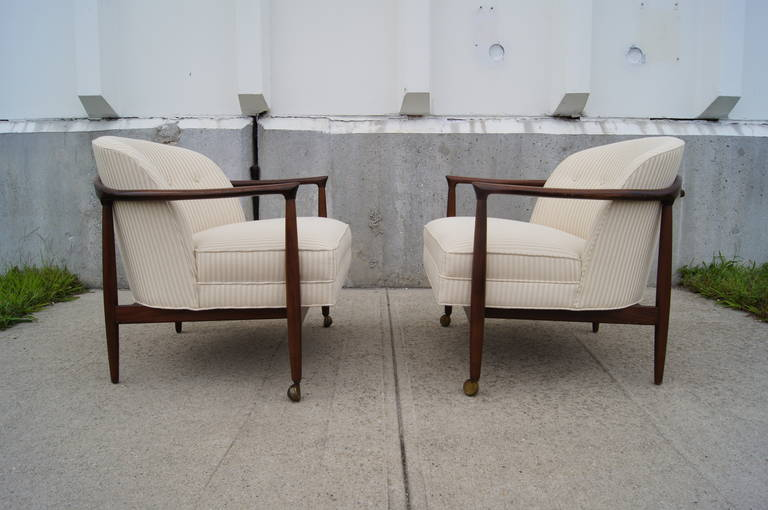 These armchairs, designed by Ib Kofod-Larsen, feature open walnut frames and newly upholstered off-white striped seats. Each chair has two casters to facilitate mobility.