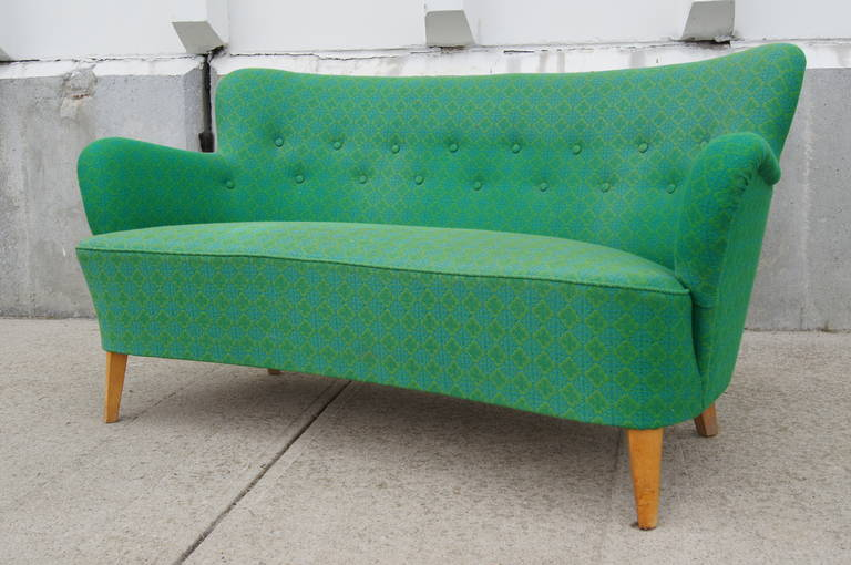 This diminutive sofa by Swedish designer Carl Malmsten for O.H. Sjögren features gently curving organic lines and a tufted back. Upholstered in a cheerful emerald green, it would make a large statement in a small space.