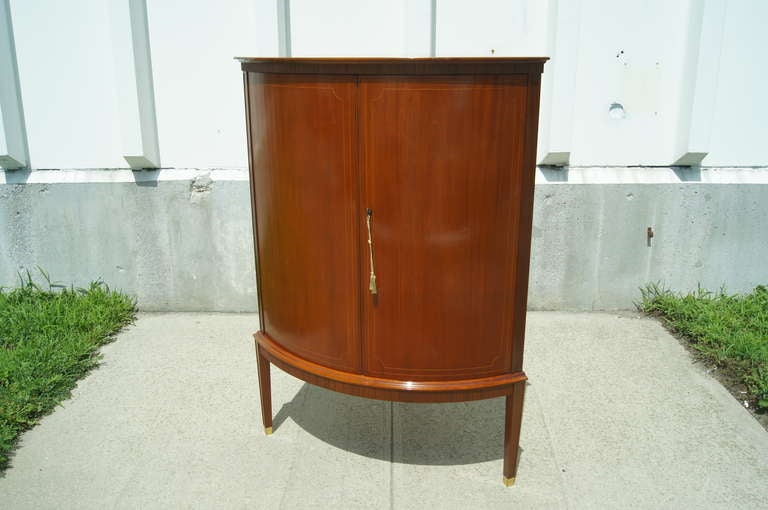 This stately Swedish cabinet of beautiful inlaid cherry fits neatly into any corner. With multiple shelves and five small drawers, it provides ample storage for unusual spaces. Its subtle federalist details, tapered legs, reeded skirt and