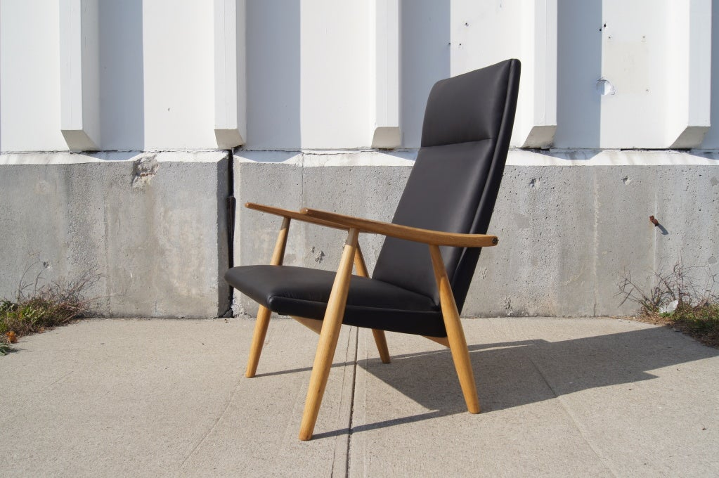 Hans Wegner designed this minimalist lounge chair, model GE-260A, for GETAMA in 1950. The solid oak frame supports a striking high back to which the tapered arms are attached with brass fittings. The spring coil system gives the chair a very