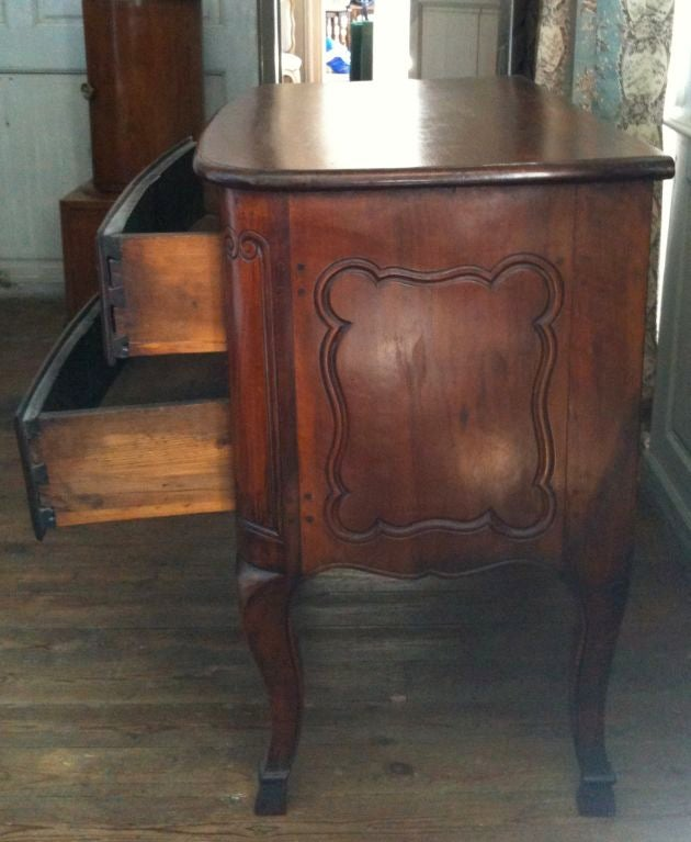 A beautiful two-drawer commode with a bow front, graceful carvings and hoof feet.