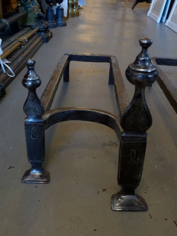 A pair of double andirons with footed bases and decorative finials. Wonderful patina.