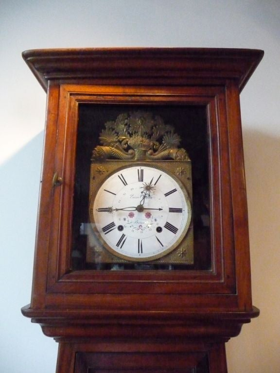 An unusual Norman fruitwood tall case clock on bracket feet with paneled inset doors.
