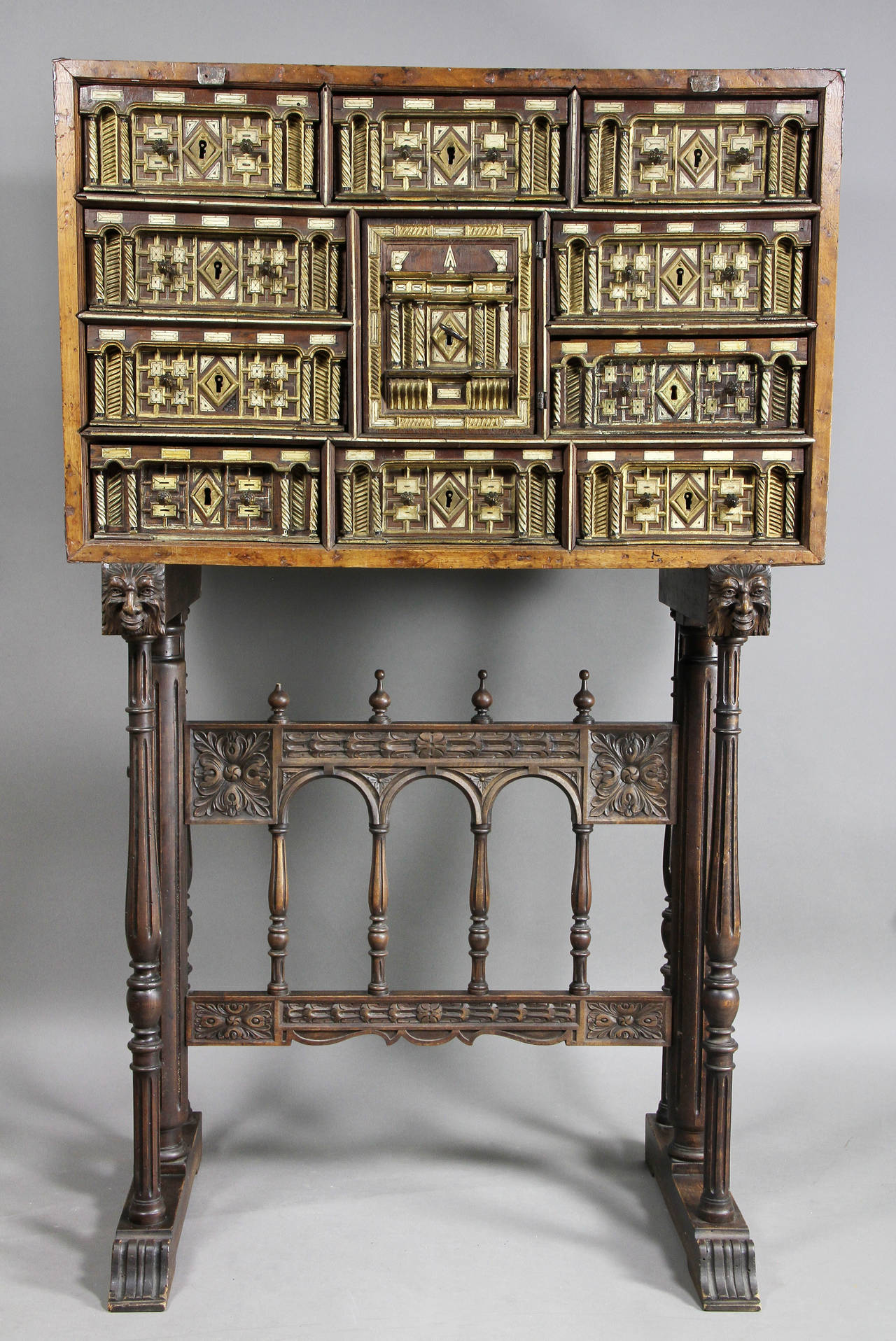 Walnut case with wrought iron strapping over many drawers and a central door enclosing drawers, later carved base of typical form.