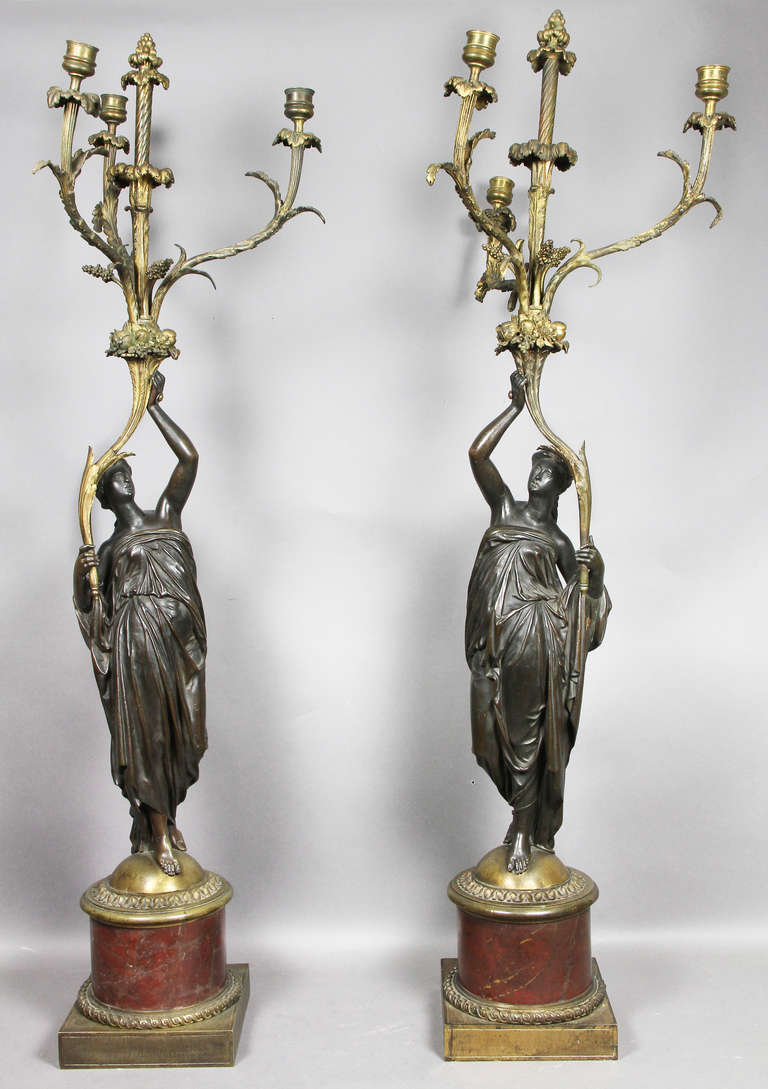 Patinated bronze female figures supporting three candle arms, raised on circular red marble section with square bases with guilloche decoration.