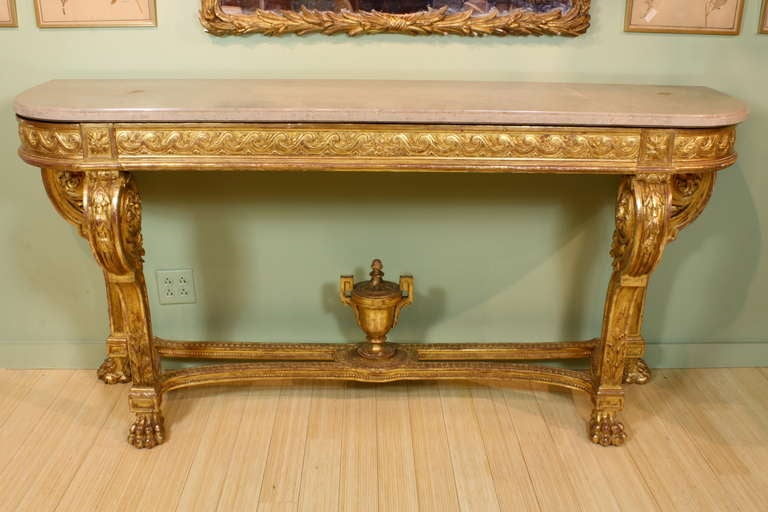 A large and impressive French giltwood console table in the Louis XVI neoclassical style (circa 1880), featuring a finely-carved vitruvian scroll apron, acanthus and laurel leaf decoration, carved Grecian urn finial on stretcher and paw feet. Table