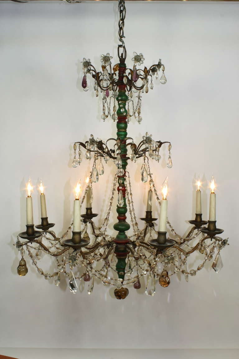 This Italian chandelier (probably from Genoa) features a turned and painted central wood column, undulating arms, tole leaves, and a vast array of clear and colored (amethyst and amber) crystals and fruit drops (including an apple suspended from the