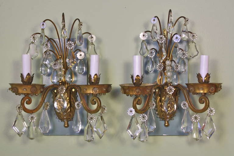 Pair of French gilt-bronze and crystal sconces by Maison Baguès.  There is a wonderful selection of interesting and high-quality crystals, particularly in the central spray. Crystal beads decorate the bottom leaf section.  The sconces also include