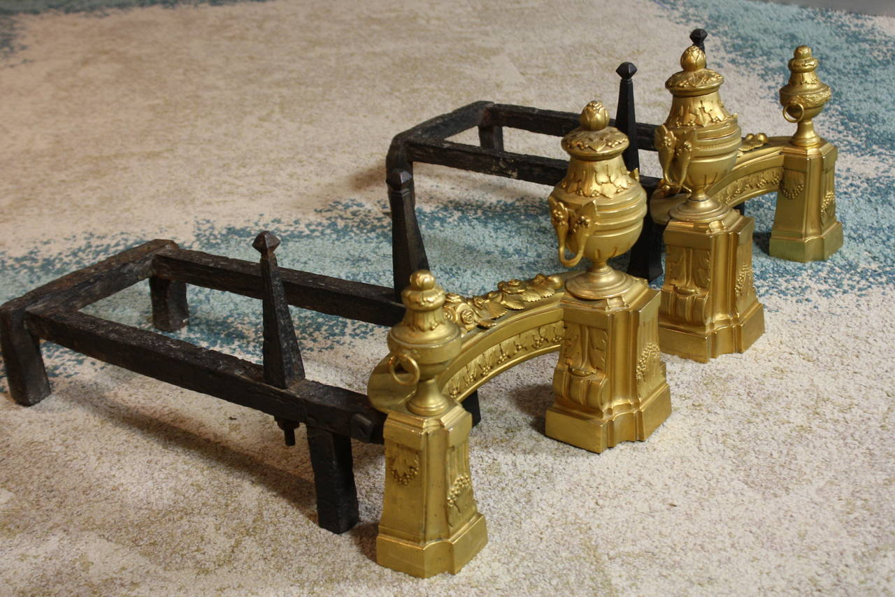 Pair of nice quality French gilded-bronze andirons or chenets, with neoclassical detailing, including urns, and swags of roses and acanthus leaves, with old forged iron bars to support logs (Louis XVI style, circa 1880).