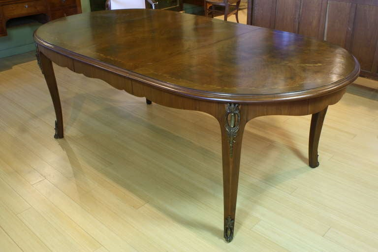 French mahogany dining table with one leaf, featuring pretty marquetry veneer floral and vine motif, cabriole legs with bronze mounts, curved apron (Louis XV style). See also our matching chairs (item number 1003) on 1stDibs. Comes with one leaf.
