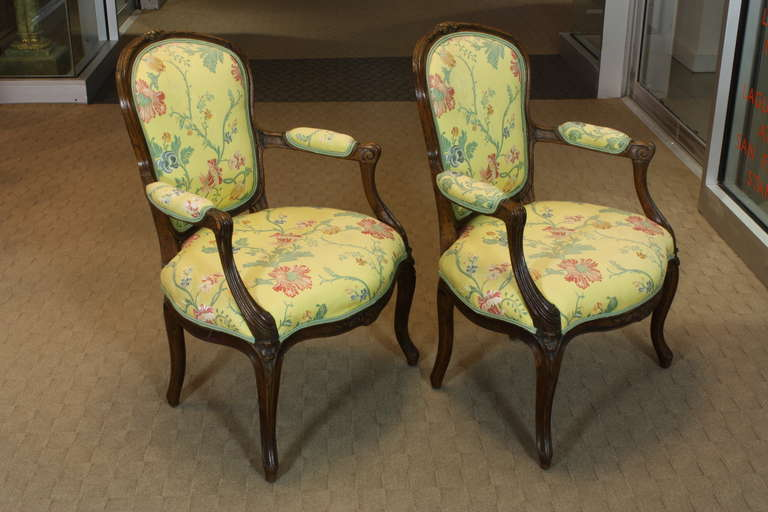 A pretty pair of French Louis XV period fauteuils, circa 1760, in carved fruitwood with floral lamps fabric. Cabriolet backs, nicely carved and molded arms, and delicately carved flowers decorating the crest rail, seat rail and knees highlight this