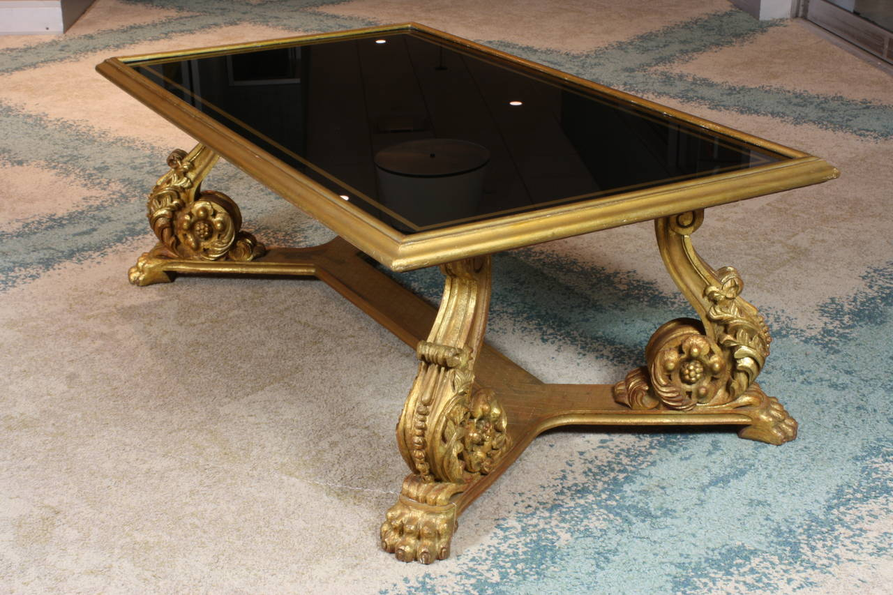 A French giltwood Baroque style coffee table, with nicely-carved acanthus decoration and paw feet, giltwood rim, and reverse painted black glass top with gilt border by Maurice Hirch (stamped underneath) (mid-20th century).