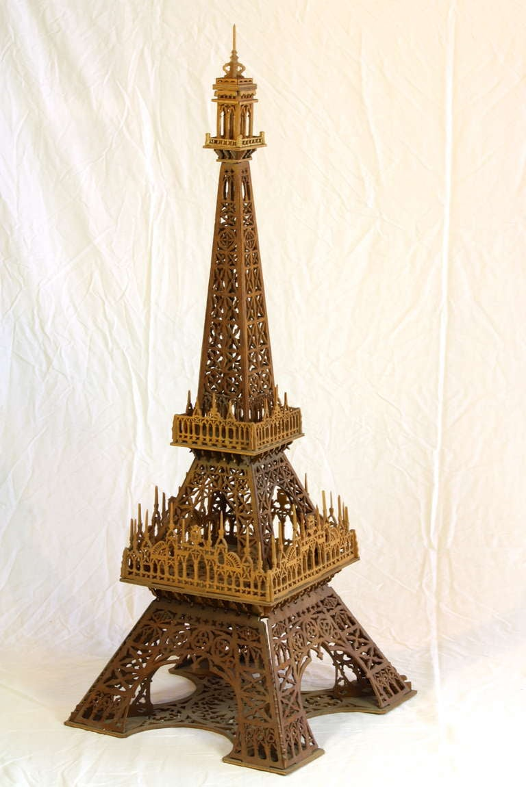 A very decorative model of the Eiffel Tower crafted out of wood.  The Eiffel Tower was constructed for the 1889 World's Fair in Paris, celebrating the centennial of the French Revolution.  This model displays the dates