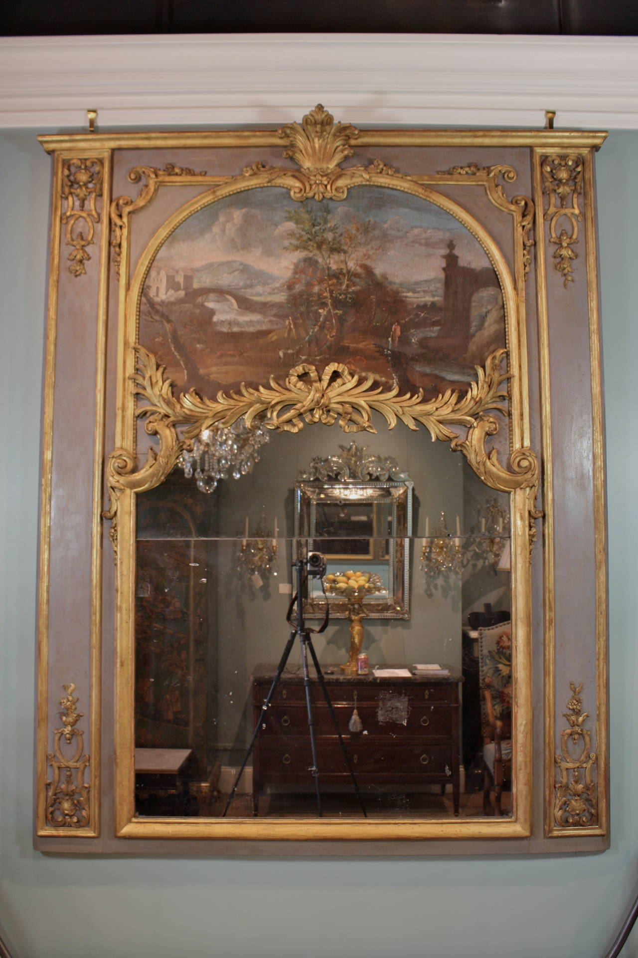 A large and impressive French, 18th century Louis XVI period carved and giltwood trumeau mirror with antique mercury glass panels. A period oil on canvas painting of an expansive landscape with hunters is enclosed in a carved giltwood arched