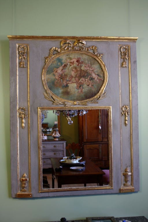 Louis XVI period parcel-gilt and polychrome trumeau mirror with a painting of Venus ringed by putti. Venus and putti are framed in a gilded oval frame with a bow on top and laurel leaves at he bottom. Gilded urns, ribbons and tassel flank the sides